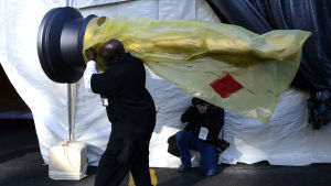 en arbetare bär på en enorm, inplastad oscarsstatyett