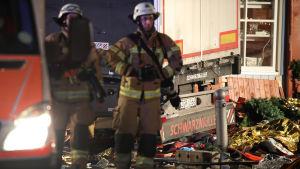 Två brandmän står vid lastbilen som körde in i en folksamling på en julmarknad i Berlin.