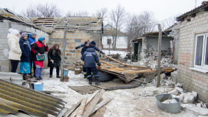 Bybor i Trudove, Donetsk, får hjälp med att riva en byggnad som skadats i granateld 18.2.2017
