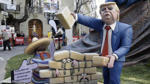 En spansk träskulptur karrikerar Donald Trump som bygger en mur mot Mexiko av tegelstenar. Människor har fastnat mellan murens tegel.
