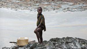 En nigeriansk pojke med ett fiskenät vid en flodbank dränkt i olja.