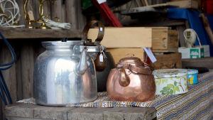Tre kaffepannor står till salu på ett bord. I bakgrunden skymtar trälådor och plåtburkar.