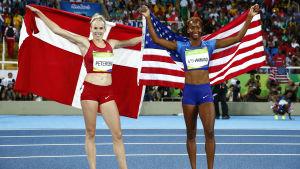 En danska och en amerikanska håller upp sina respektive länders flaggor efter häcklopp.