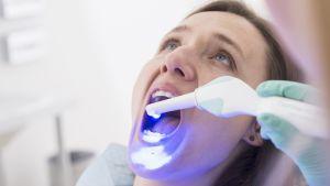 Kvinna gapar hos tandläkaren.