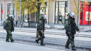 Tre stycke bombtekniker går utanför köpcentret Ro' Torv i Roskilde som evakuerades på grund av bombhot.