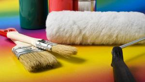 Målarpenslar, en roller och målfärg ligger på en regnbågsfärgad yta.