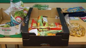 Överbliven mat från serveringen delas ut till dm som behöver.