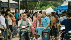 tre gubbar åker moped med sidovagn genom ett myller av människor.
