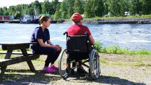 En äldre person vid flodstranden tillsammans med en yngre person.