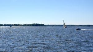Motorbåtar och segelbåt i skärgården.