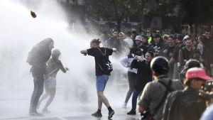 Polisen sprutar vatten på demonstranter.