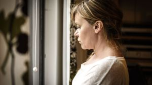 Kvinna tittar ut genom fönster.