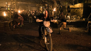 Vin Diesel kör motorcykel bort från en klunga människor.