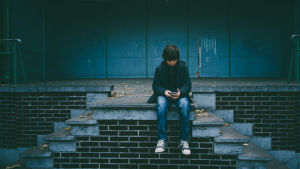 Pojke sitter med telefon på trappa.