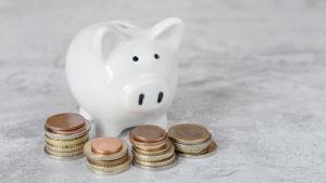 En spargris står bakom små högar av euromynt.