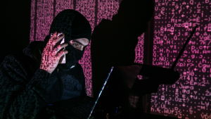 Man i rånarluva framför en projicerad bild av datorkod