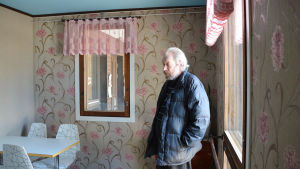 Ortsbon Christer Alm i nyrenoverade baren i Isnäs, fönstren har rosa spetsgardiner och väggen blommig tapet