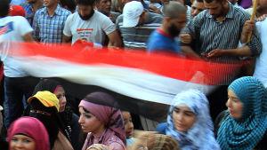 Kvinnor skyddas av män under en demonstration.