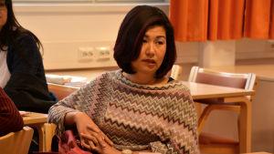 Thuy Le Luu sitter på en stol vid ett bord i ett klassrum