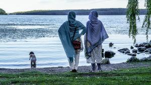 Två kvinnor i slöja står på en sjöstrand och övervakar ett litet barn som plaskar i vattnet.