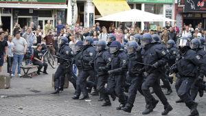 Många poliser i kravallutrustning springer på en gata.