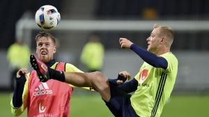 Pontus Jansson (t.v.) nickar bollen medan John Guidetti försöker bryta under en träning.