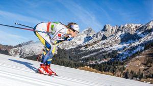 Stina Nilsson skidar ner för en backe med vackra bergvyer i bakgrunden.
