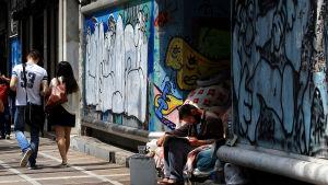 En hemlös man läser tidningen utanför en stängd butik i Aten, Grekland.