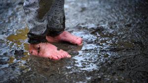 Fötter i lervällingen i Idomeni i Grekland.