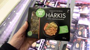 En hand håller upp ett paket Härkis ovanför kyldisken med liknande produkter.