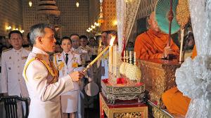 Kronprins Maha Vajiralongkorn tänder ljus vid en religiös ceremoni efter kung Bhumibols död