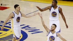 Klay Thompson (t.v.), Stephen Curry (nere) och Kevin Durant tar varandra i händerna.