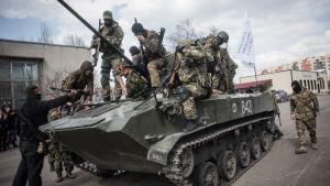 Proryska beväpnade män och ett pansarfordon i Slovjansk