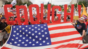 """Tea Party-rörelsens demonstrerar mot Obamas häslovårdsreform och deltagare håller upp en stor text """"det är nog"""" över Amerikas flagga."""