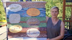 Linda Boberg-Santala visar upp Världsbymattan.