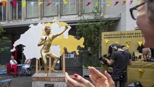 """Kim-Fabian von Dall'Armi """"Den gyllene pojken"""" läser upp de första resultaten av den schweiziska folkomröstningen om basinkomst."""