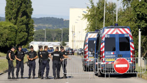 Poliser utanför gasfabriken nära franska Lyon där en man halshöggs 26.6.2015.