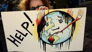En kvinna håller upp en skylt med en svettig jordglod på, på en demonstration.