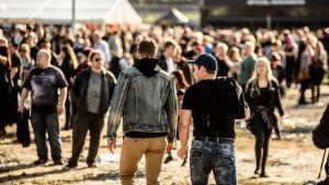 Två personer går mot en folkmassa på festivalen Rock Fest