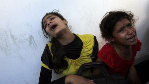 Palestinska flickor sörjer sin far som dog i den israeliska attacken mot en FN-skola i Gaza den 24 juli.
