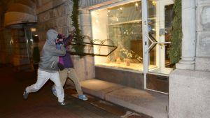 Ungdomar krossar butiksfönster