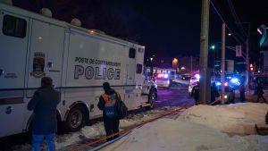En polisbil och i bakgrunden flera räddningsfordon utanför en moské i Quebec, Kanada, där fem personer uppges ha dött i en skjutning.