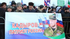 Män håller upp skylt med texten Kadyrov - en rysk patriot.