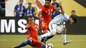 Lionel Messi och Arturo Vidal kämpar om bollen i finalen i Copa America.