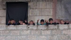 Barn visar segertecknet i stadsdelen Salah al-Din i östra Aleppo 16.12.2016