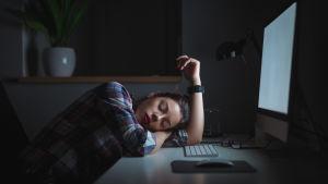 nainen nukkuu työpöydän ääressä