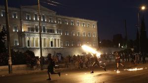 Demonstranter kastar bensinbomber vid parlamentet i Aten.