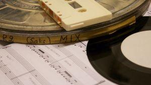 vinyylilevy, nuotit, magneettikela ja c-kasetti pöydällä lomittain
