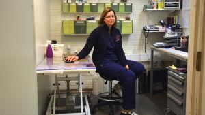 Veterinär Marina Hulthom sitter på sitt rum på kliniken. Rummet är ganska litet och har ett undersökningsbord och ett skrivbord. Väggarna är vita.