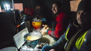 flyktingar lagar mat inne i tält